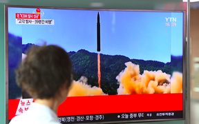 A woman walks past a television screen in the South Korean capital Seoul showing a picture of North Korea's launch of an intercontinental ballistic missile.
