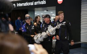 Team NZ crew members, from left, Glenn Ashby, Peter Dalton and Peter Burling, bringing the America's Cup trophy home.