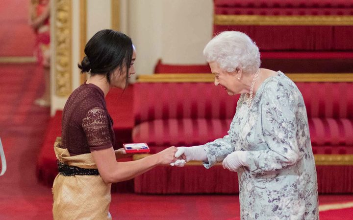 Elizabeth Kite  receives her award from the Queen.