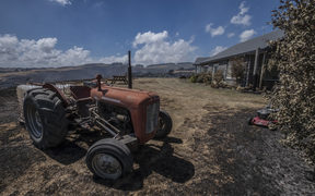 A tractor stands nearly intact after fire raged around this property in the Port Hills