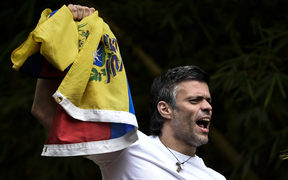 Leopoldo Lopez waves a Venezuelan flag on top of a wall outside his house in Caracas, hours after his release on Saturday 8 July 2017 (Venezuelan time).