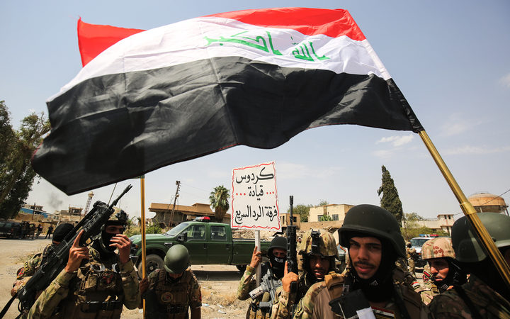 Members of the Iraqi federal police wave national flags during a military parade as they celebrate in the Old City of Mosul, where the gruelling battle to retake Iraq's second city from Islamic State (IS) group fighters is now nearing its end, on July 2, 2017.
