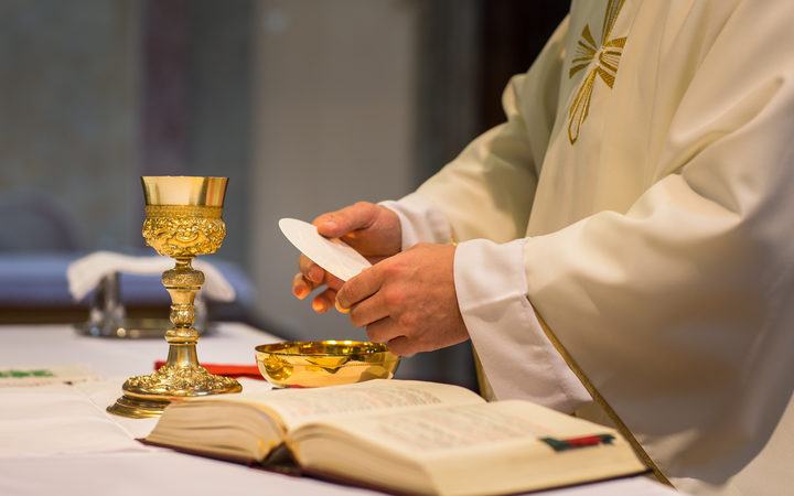 Bread and wine are used to celebrate the Eucharist during Roman Catholic masses. Here, a priest holds a wedding ceremony mass.