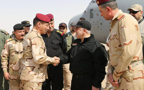 Iraqi Prime Minister Haider al-Abadi (C-R) shaking hands with army officers upon his arrival in Mosul