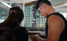 Passengers check flight information in the international terminal at Bali's Ngurah Rai airport in Denpasar.