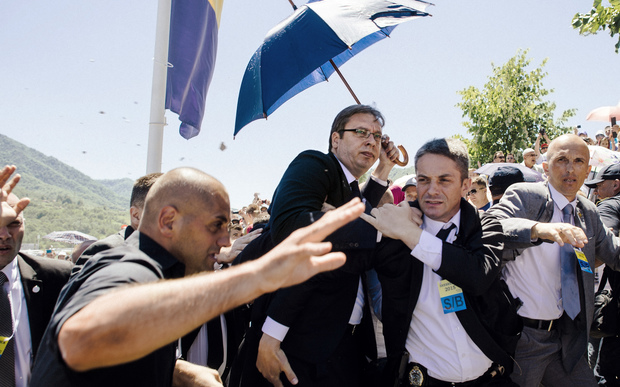 Bodyguards try to protect Serbian Prime Minister Aleksandar Vucic (centre) from stones hurled at him by an angry crowd.