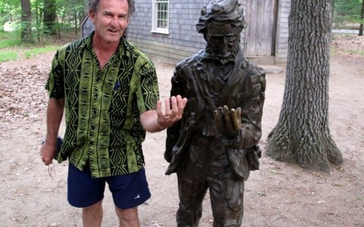 Kennedy Warne standing beside a statue of Henry David Thoreau