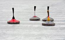 Stock photo of curling stones during an outdoor bonspiel.