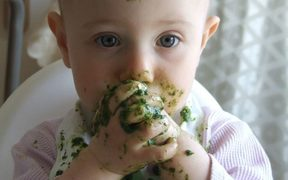 A photo of a toddler eating messy green food with her fingers