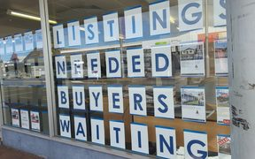 A sign in a real estate window in Dargaville, looking for house listings.