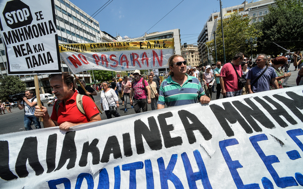 Protestors hold a banner during a peaceful march in central Athens, marking a 24-hour public sector workers' strike.
