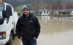 Craig Miller stands next to the flooding at a Dunedin subdivision.