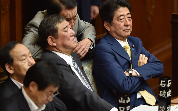Japan's Prime Minister Shinzo Abe (right) and members of his cabinet attend a parliamentary session about the controversial security bills.