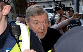 Cardinal George Pell arrives under heavy police protection for a filing hearing at the Melbourne Magistrates Court after being charged with sexual assault offences in Melbourne, July 26, 2017.