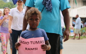 "A boy hold a sign bearing the words ""Thank you very much, RAMSI"""