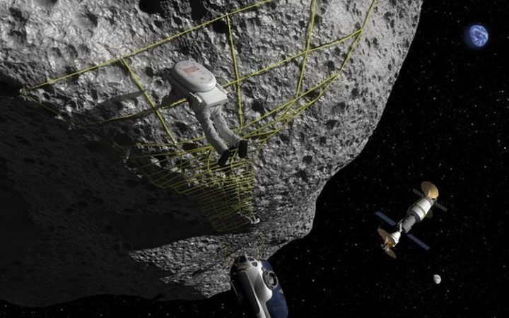 In this artist's concept an astronaut performs a tethering maneuver at an asteroid.