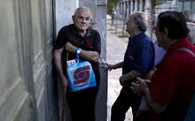Pensioners wait outside a branch of the National Bank of Greece to receive their benefits, limited to €120, in Athens on 17 July 2015.