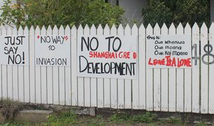 A fence in Whatuwhiwhi with sings on it expressing objection to foreign development.