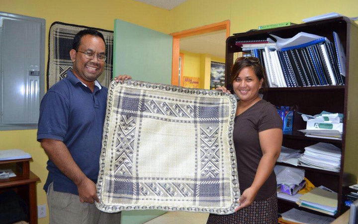 Mattlan Zackhras and his wife Angela show off a fine woven mat made by a youthful trainee from his home atoll of Namdrik in this file photo from 2013.