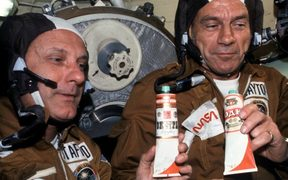 "NASA astronauts enjoying fake ""vodka"" – Russian vodka labels pasted on top of  borscht tubes. Public domain. (not quite beer)"
