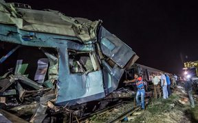 Emergency personnel and Egyptian military police search the wreckage of the train collision.