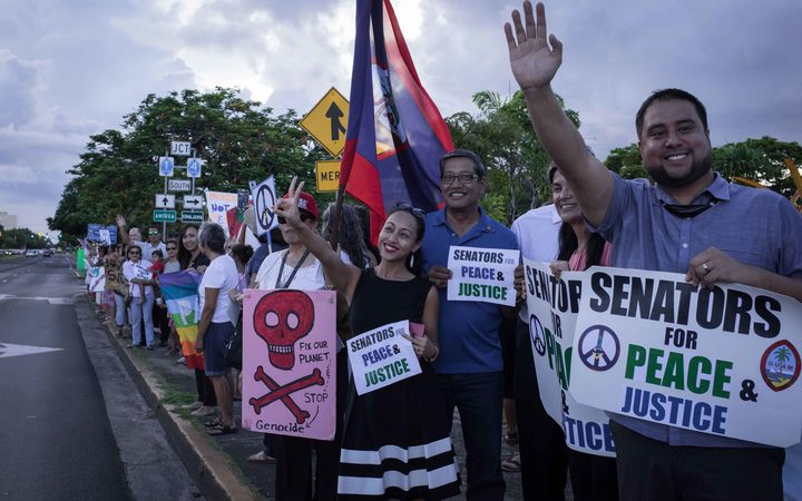 "Members of community groups calling for the ""de-colonization and de-militarization of Guam"" attend a rally for peace in Guam."