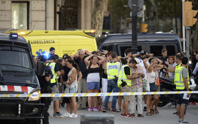 Police check the identity of people after a van ploughed into a crowd in Barcelona.