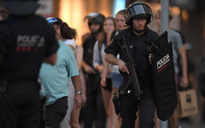 Spanish policemen stand guard in a cordoned off area after a van ploughed into the crowd, killing 13 persons and injuring over 50 on the Rambla in Barcelona on August 17, 2017.