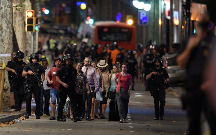 Policemen accompany clients of a store outside a cordoned off off area after a van ploughed into the crowd, killing 13 persons and injuring over 80 on the Rambla in Barcelona on August 17, 2017.