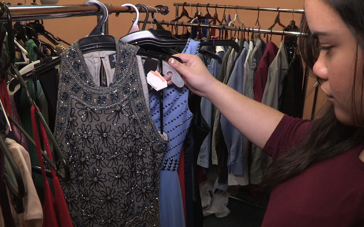 A student at James Cook High School looking at ball gowns made available so all students can attend the school ball.