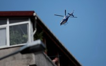 A police helicopter hovers during the funeral at Gazi Street in Istanbul for three of those killed in Suruc.