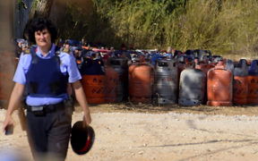 A policewoman in front of dozens of gas bottles in Alcanar during a search linked to the Barcelona and Cambrils attacks.