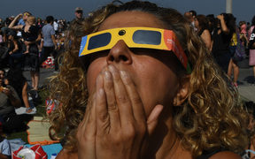 Cherri Haghighit views the start of the total solar eclipse at the Griffith Observatory in Los Angeles, California, on August 21, 2017.