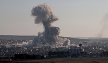 Smoke rises after a US-led coalition air strike on IS targets in Kobane in Syria (December 2014).