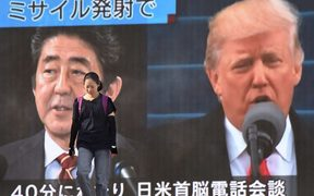 A woman walks in front of a huge screen displaying Japanese Prime Minister Shinzo Abe (L) and US President Donald Trump (R) in Tokyo.