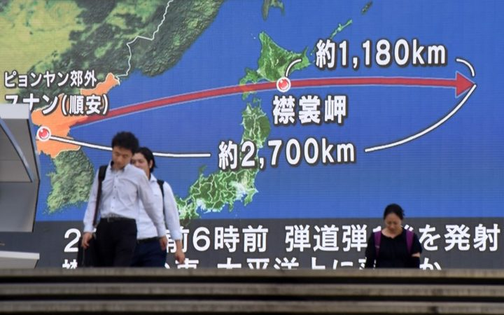 Pedestrians walk in front of a huge screen displaying a map of Japan (R) and the Korean Peninsula, in Tokyo.