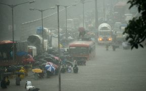 Mumbai residents wade through a flooded street during heavy rain showers on 29 August.