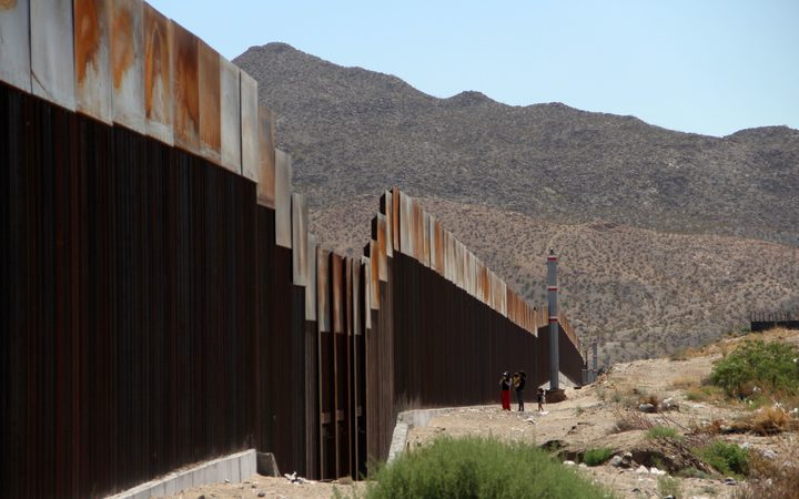 Parts of the US-Mexico border are already sealed off by a wall. A family is pictured standing on the Mexican side of the wall in 2017.