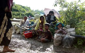 A Rohingya family sit beside a road in Nykkhongchhari, Bangladesh after fleeing violence in Myanmar.