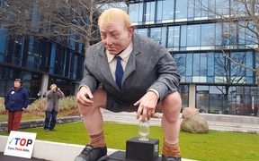 Protesters have delivered a huge statue of Environment Minister Nick Smith squatting over a glass of water to Canterbury's regional council.