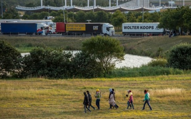 Migrants try to enter inside the Eurotunnel site to attempt to reach Britain, in Coquelles near Calais, northern France, on July 31, 2015.