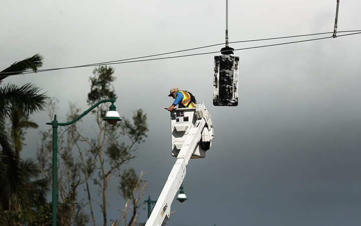 An electrical worker repairs traffic lights in Naples, Florida after Hurricane Irma swept through on 11 September, 2017.