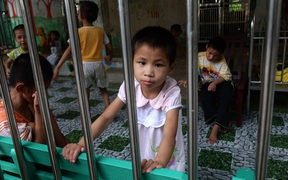 A young girl looks at visitors inside a state-run orphanage on the outskirts of Hanoi, Vietnam in September 2014.