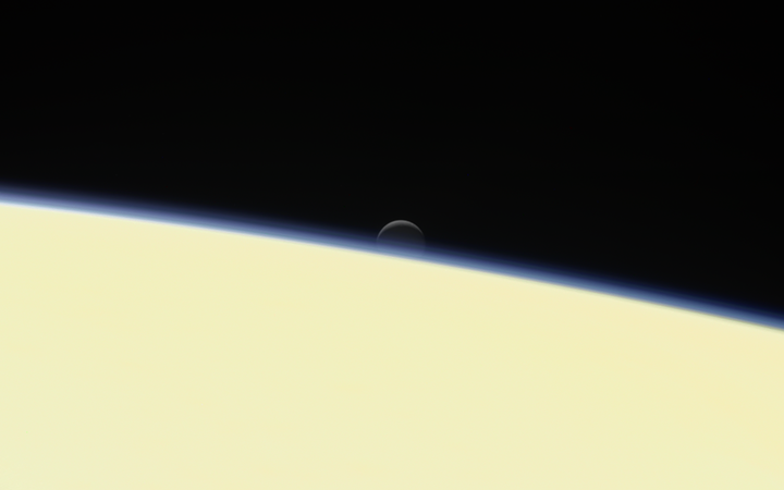 Saturn's active, ocean-bearing moon Enceladus sinks behind the giant planet in a farewell portrait from NASA's Cassini spacecraft.