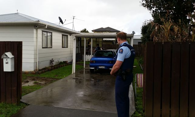 Armed police guard the family home in Mangere while the search continues.