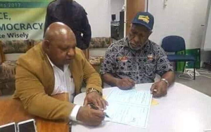 William Powi signs the election writ after winning back the Southern Highlands regional seat in Papua new Guinea.