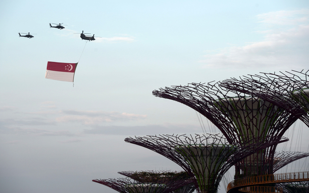 A Chinook helicopter (top R) from the Republic of Singapore Air Force flies a giant national flag over the Garden by the Bay dome