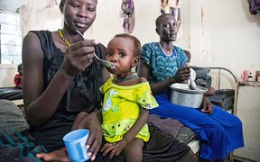 A mother gives food to her child with malnutrition in a clinic in Old Fangak, Jonglei state
