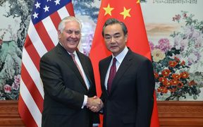 US Secretary of State Rex Tillerson shakes hands with Chinese Foreign Minister Wang Yi.