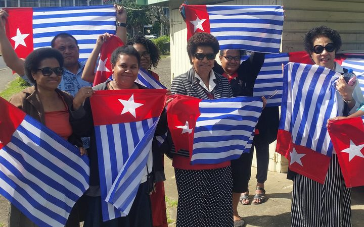 Ro Teimumu Kepa (centre) with staff flying the West Papua flag.